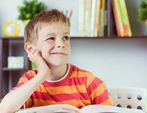 Elementary school boy at desk reading boock. Elementary school boy at classroom desk reading boock royalty free stock photos