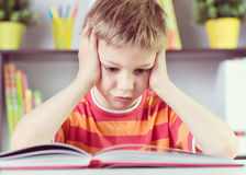 Elementary school boy at desk reading boock stock images