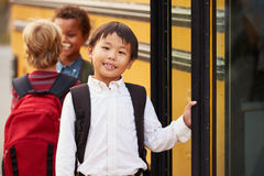Elementary school boy at the front of the school bus queue Stock Image