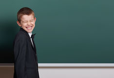 Elementary school boy make faces near blank chalkboard background, dressed in classic black suit, one pupil, education concept Royalty Free Stock Photography