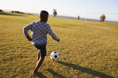 Elementary school boy playing football in an open field Royalty Free Stock Images