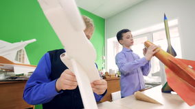 Elementary school boys assembling constructor models of the plane and the model of the rocket. 4K. Elementary school boys examinating models of the plane and stock video footage