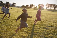 Elementary school boys and girls running in an open field Royalty Free Stock Image