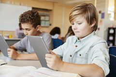 Elementary school boys using tablet computers in class stock photography
