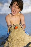 Elementary school child making sand castle Stock Image