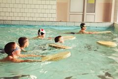 Elementary school children within swimming skills lesson. stock images