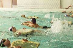 Elementary school children within swimming skills lesson. royalty free stock photo