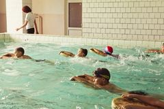 Elementary school children within swimming skills lesson. royalty free stock photography