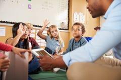 Elementary school class sitting cross legged using tablets Stock Photos