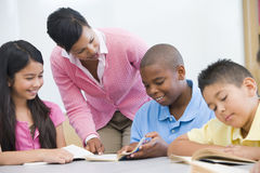 Elementary school classroom. Teacher helping elementary school reading group Royalty Free Stock Photo