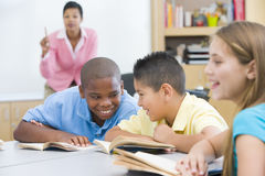Elementary school classroom. Two boys misbehaving in elementary school classroom Royalty Free Stock Photography