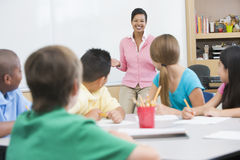 Elementary school classroom with teacher. Standing at board Royalty Free Stock Images