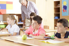 Elementary school classroom. Teacher helping elementary school group Stock Image