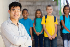 Elementary school educator. Handsome male elementary educator with students on background Royalty Free Stock Image