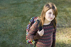 Elementary school girl with her bookbag. Girl (11 years) carrying school backpack, looking at camera with serious expression Royalty Free Stock Images