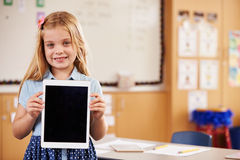 Elementary school girl holding a tablet computer, portrait Stock Image