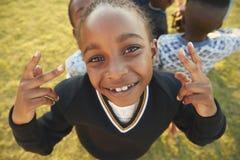 Elementary school girl posing to camera outdoors, high angle Stock Photos