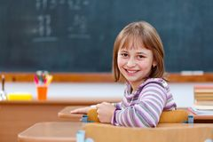 Elementary school girl turning back and smiling Stock Image