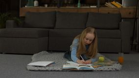 Elementary school girl writing her homework. Lovely blonde grade school girl drinking orange juice while doing her homework at home. Little attractive blonde stock footage