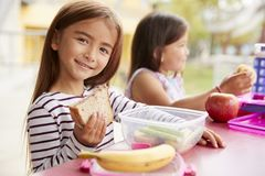 Elementary school girls eating at school lunch table royalty free stock photography