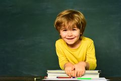 Elementary school. Happy mood smiling broadly in school. First school day. Kid is learning in class on background of. Blackboard royalty free stock image