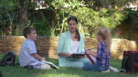 Elementary school, happy schoolkids boy and girl with tutor woman read classbook and chat during training on grass. Outdoors stock footage