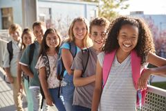 Elementary school kids with backpacks smiling at the camera stock photos