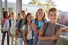 Elementary school kids with backpacks smiling to the camera stock photos