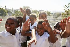 Elementary school kids in playground waving to camera Royalty Free Stock Photography