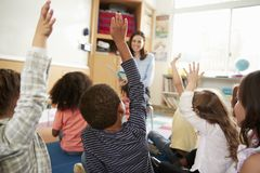 Elementary school kids raising hands to teacher, back view royalty free stock photo