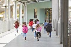Elementary school kids run from camera in school corridor stock photo