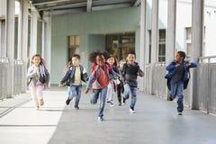 Elementary school kids running in a corridor in the school stock photo