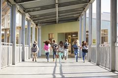 Elementary school kids running in school corridor, back view royalty free stock photography