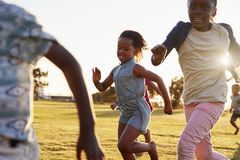 Elementary school kids running in an open field, close up Stock Images