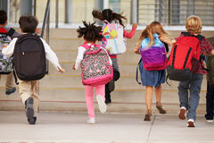 Elementary school kids running into school, back view Stock Photos