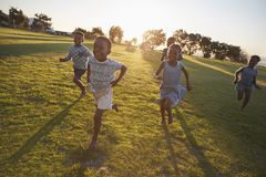 Elementary school kids running to camera in an open field Stock Images