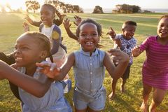 Elementary school kids running to camera outdoors, close up Stock Photography