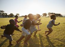 Elementary school kids running together in an open field Royalty Free Stock Image