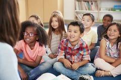 Elementary school kids sit on floor looking up at teacher stock photography