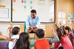 Elementary school kids sitting around teacher in a classroom Royalty Free Stock Image