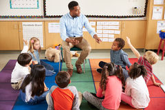 Free Elementary School Kids Sitting Around Teacher In A Lesson Royalty Free Stock Images - 71530089