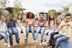 Elementary school kids sitting on carousel in the schoolyard royalty free stock images