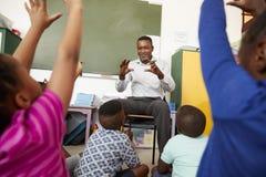 Elementary school kids sitting on floor listening a teacher Stock Photos
