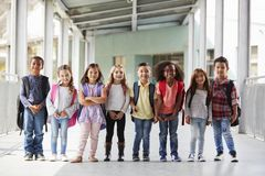 Elementary school kids stand in corridor looking at camera stock photo