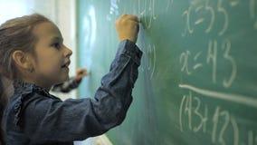 Elementary school. Little schoolgirl writing numbers on green chalk board in classroom