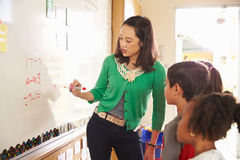 Elementary school maths class at the whiteboard with teacher Royalty Free Stock Photo