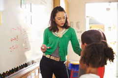 Elementary school maths class at the whiteboard with teacher Stock Photography