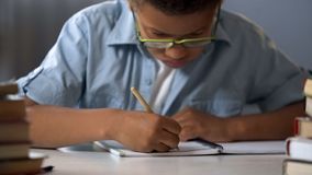Elementary school pupil diligently writing letters in his notebook, calligraphy. Stock photo stock photos
