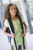 Elementary school pupil outside building. With backpack Stock Photo
