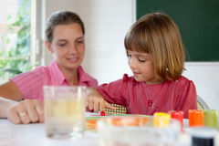 Elementary school pupil painting with a teacher Stock Photography